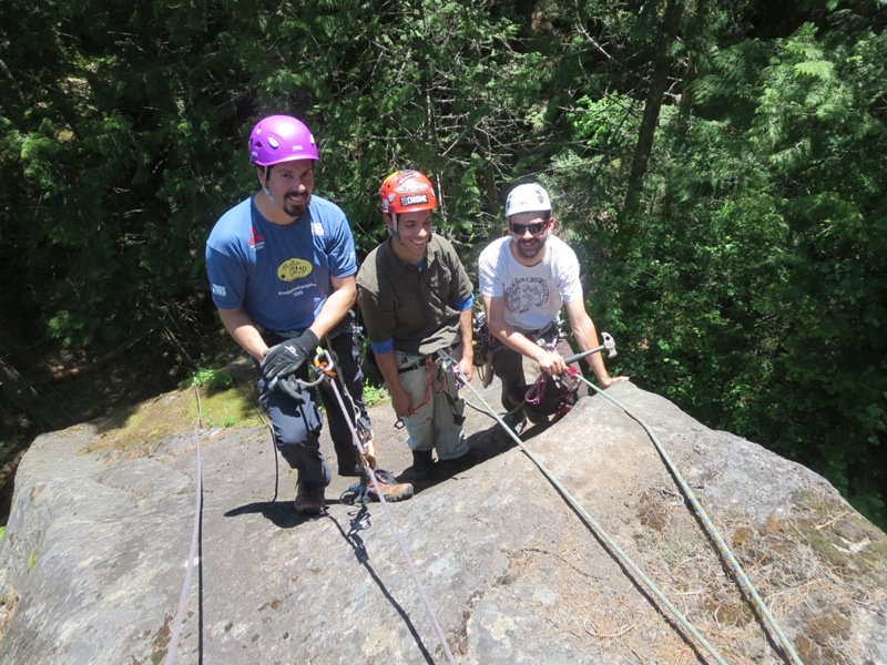 Three men work hard building a rock climbing route in Ymir, British Columbia